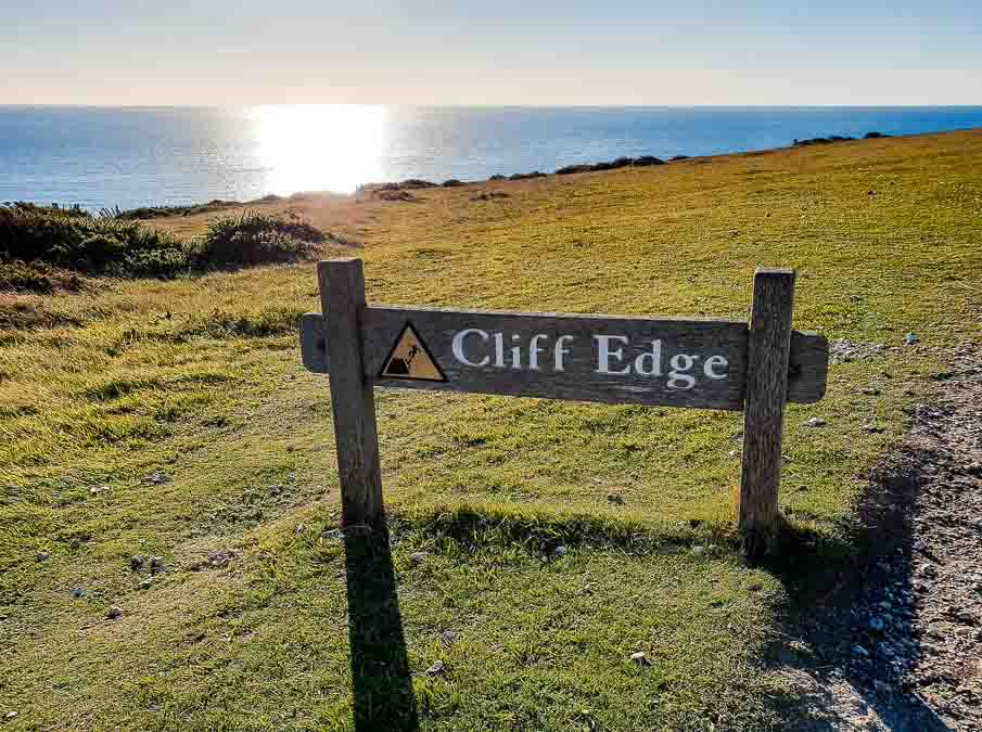 Cliff edge sign with sea in the background