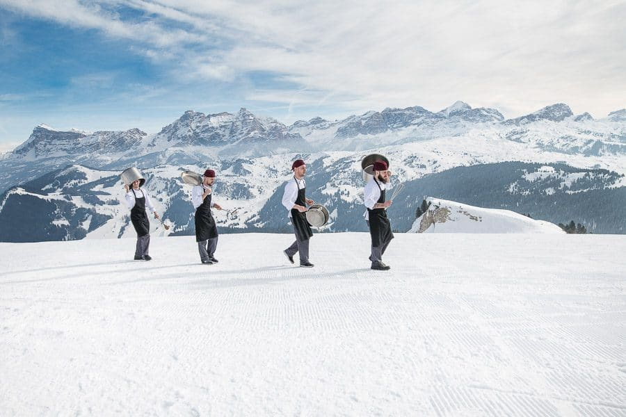 four chefs on the snow with mountain backdrop