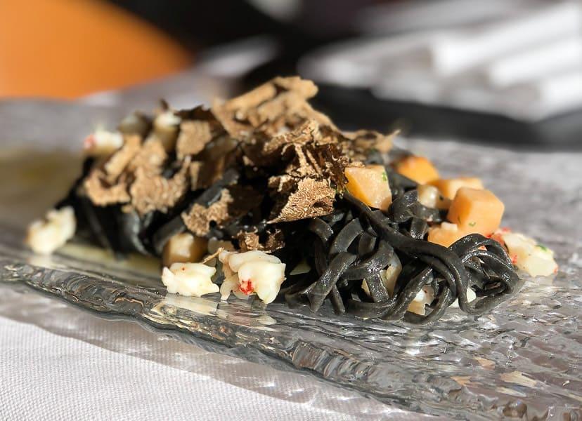 Tagliolini with cuttlefish, prawns, apples on carpaccio of scallops and black truffle