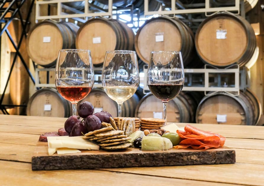 wine and charcuterie with barrels in background