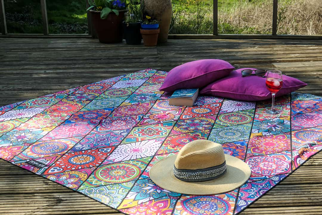 Colourful beach towel with hat and pink cushions