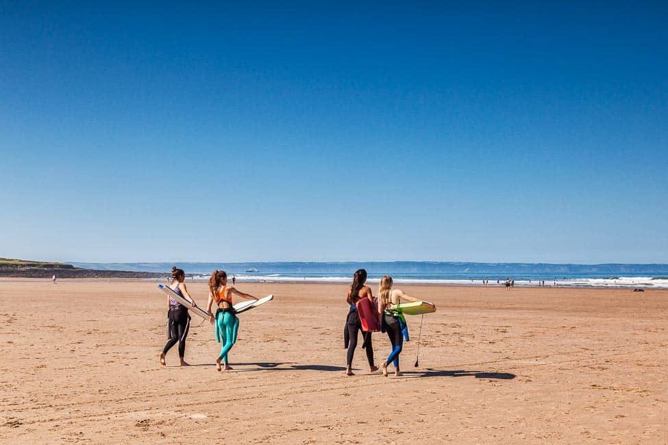 Surfer girls walking down Croyde Beach, Devon
