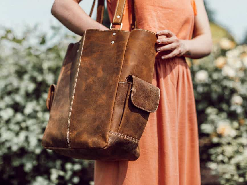 woman holding brown leather tote bag