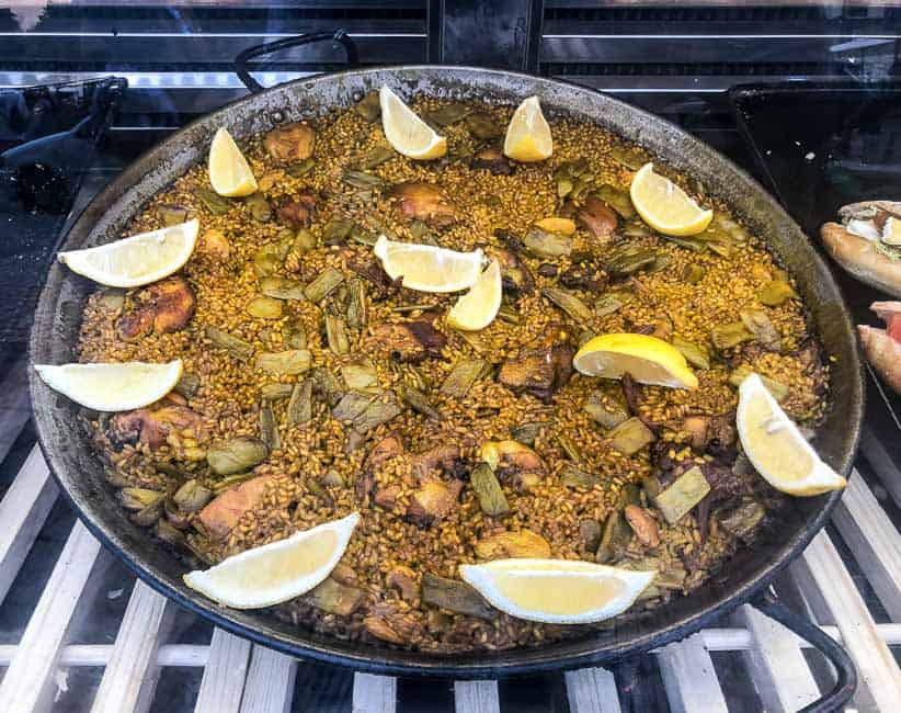 Valencian Paella in paella pan with lemon wedges