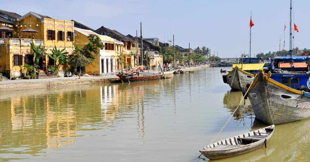 Thu Bon River, Hoi An with yellow houses reflecting on the water