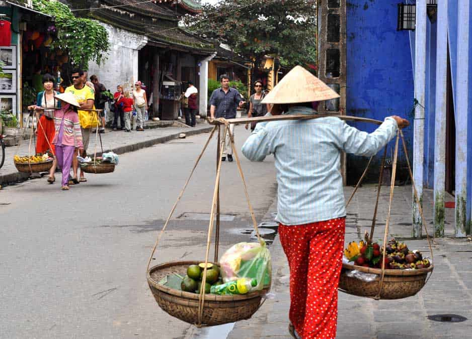 Vietnamese woman walking with baskets and non la hat